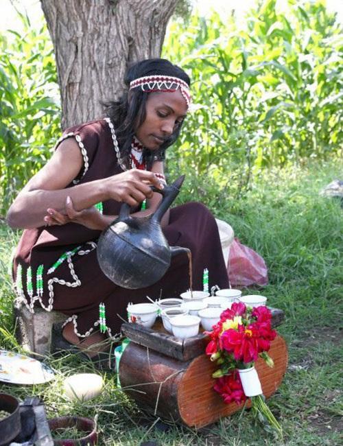 Женщина наливает кофе из джебены в финджаны фото